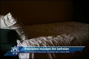 Per Haftbefehl Gesuchter versteckt sich unterm Bett: Polizisten müssen ihn befreien
