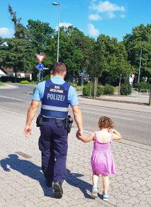 Gunst der Stunde genutzt: Dreijährige büxt aus und wird von Polizisten an der Hand genommen