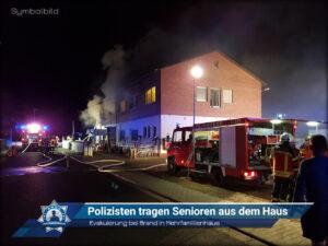 Evakuierung bei Brand in Mehrfamilienhaus: Polizisten tragen Senioren aus dem Haus