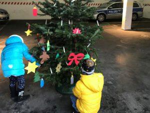 Selbstgebastelter Schmuck: Kinder schmücken Weihnachtsbaum der Polizei